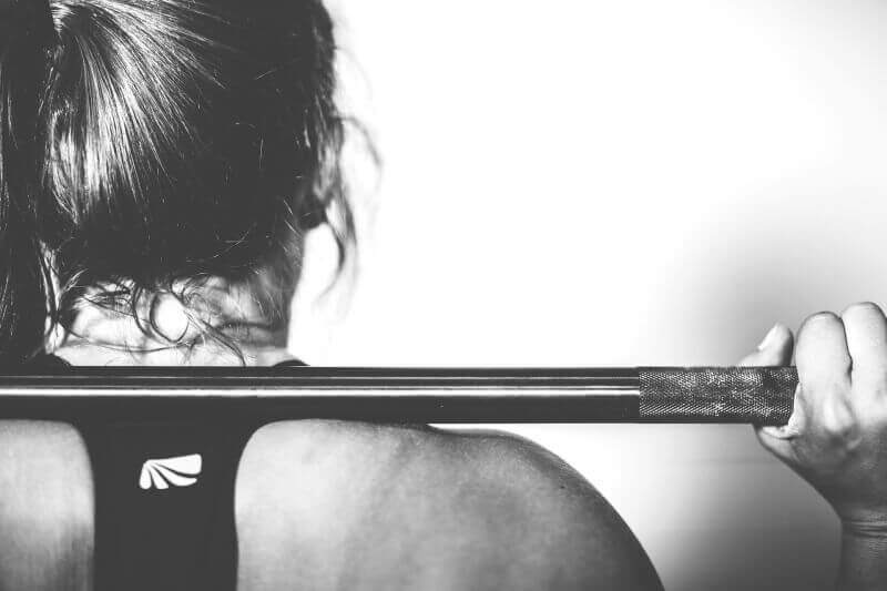 Black and white close-up of a woman lifting a barbell.